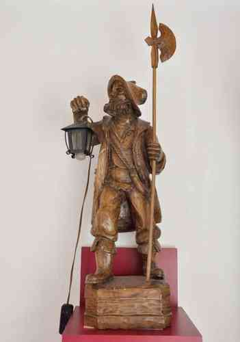 Wood sculpture night watchman with a lantern illuminated